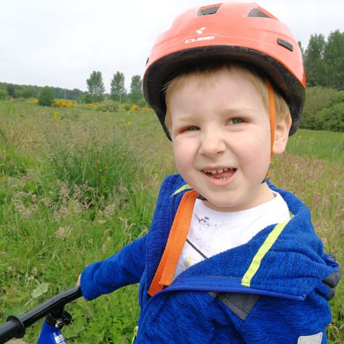 child riding a bike with helmet on