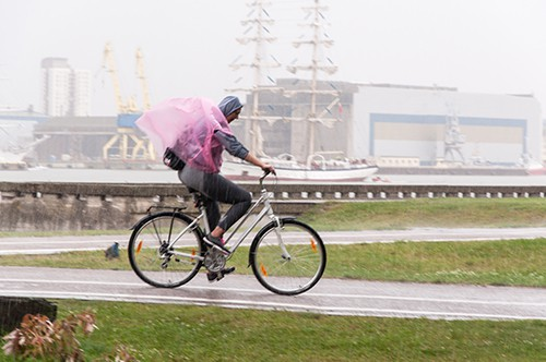 Woman is commuting on bicycle during heavy rain.