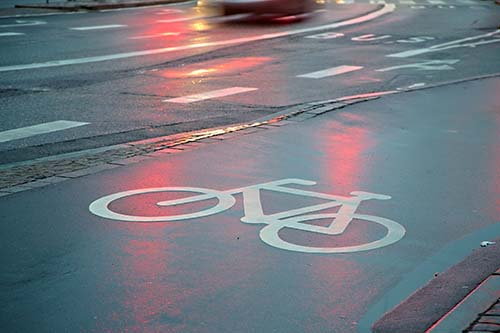 Bicycle lane sign on wet asphalt surface