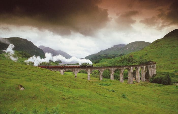 A STEAM TRAIN ON THE WEST HIGHLAND LINE CROSSES THE VIADUCT SPANNING GLEN FINNAN, AS IT APPROACHES THE VILLAGE OF GLENFINNAN, WITH LOCH SHIEL VISIBLE BEHIND, HIGHLAND.