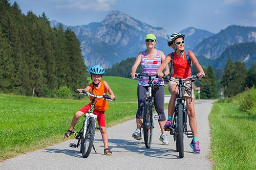 Family of three riding bikes in the mountains